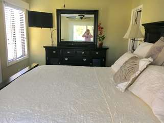 The master bedroom boasts a mounted HDTV, hardwood floors and en suite bathroom.