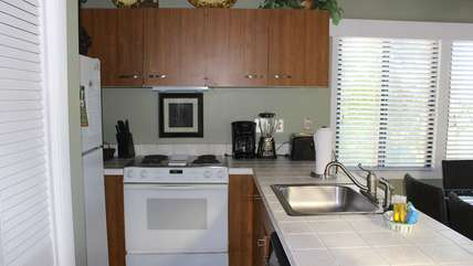 It has white tile countertops and is fully equipped.