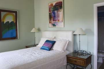 The 2nd bedroom has a queen bed and a high ceiling with fan.