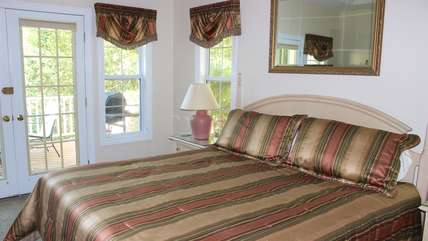 The master bedroom has a king bed, deck access, and views of the lake.