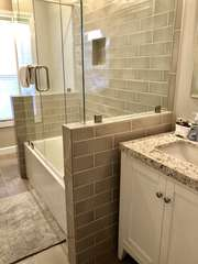 Totally remodeled guest bathroom is beautiful - has a shower/tub combination.
