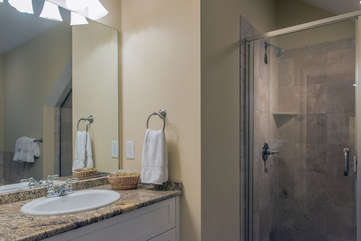 There is a full bath next to this bedroom. It has a large tile shower.