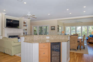 The open kitchen has a counter with seating for two & a wine cooler.