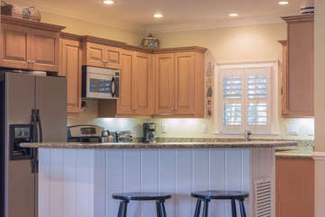 The kitchen island has additional seating on one side and a wine refrigerator on the opposite side.