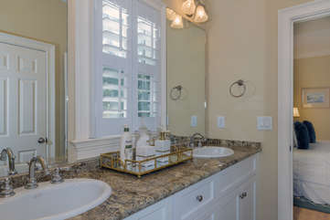 The master bath has a two sink vanity, granite counters, and a walk-in shower.