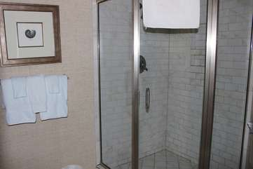 The corner shower is tiled and roomy.