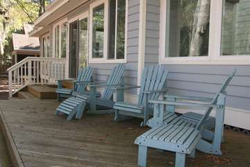 Outside, there are Adirondack chairs on the wood deck shaded by trees.