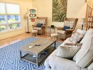 The living room has a wall of windows overlooking the dunes and water.