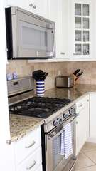 There is a gas stove with convection oven and a microwave.