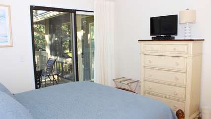 The 2nd bedroom has a queen bed, small TV, and doors to the deck.