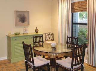 The dining area has a round glass topped, wicker table that seats 4.