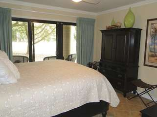 The master bedroom has a king bed and sliding doors to the covered patio.
