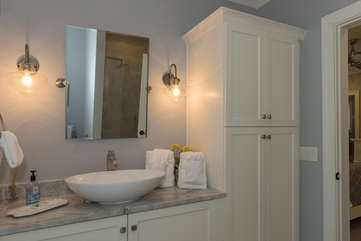 The attached bath has a vessel sink set in a quartzite counter.