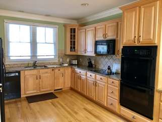 Enjoy cooking in this large kitchen featuring cherry cabinets and granite counters.