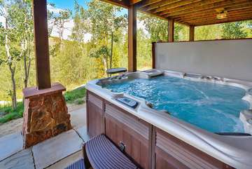 Spacious Hot Tub with custom lighting and stone patio