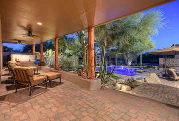 Covered patio with cozy furniture and amazing views of the pool and the vibrant southwest