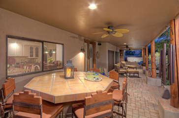 Covered patio runs length of house providing shade and ideal places to gather