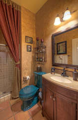 Third bath with walk-in shower is decorated in bold southwest colors