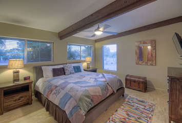 Stylish west master suite with king bed, exposed beam and large windows