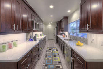 Kitchen has custom cabinets, stainless steel appliances and granite counters