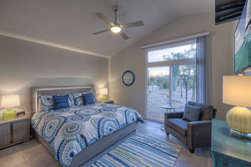 Fourth bedroom has queen bed, TV and doors that exit to front of home