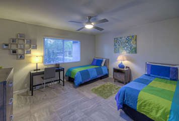 Trendy third bedroom has extended length twin beds, TV and desk