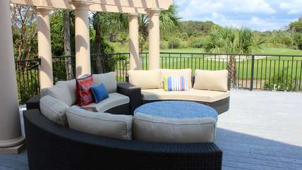 Relax under the pergola on the cushioned chairs.