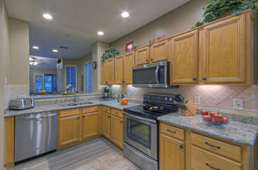 Custom kitchen with new stainless steel appliances and new granite counter tops is fully stocked for preparing and serving meals