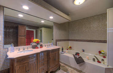 Bath in north master pool side suite has dual vanity sinks, separate shower and soothing jacuzzi tub