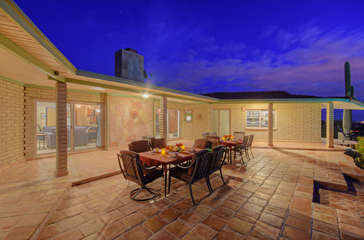 Lovely covered patio has comfortable funishings for lounging and dining outside against a backdrop of sensational desert and mountain vistas