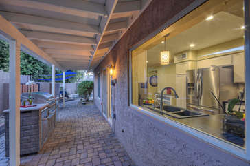 Covered stone walkway with built-in barbecue connects front and back of home