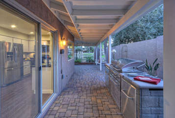 Covered patio on side of home provides access to backyard and features built in gas grill and charming porch swing