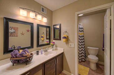 Master bath has dual vanity sinks and enclosed tub/shower combination and commode