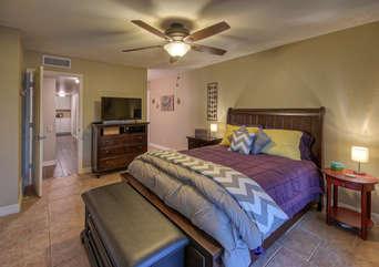 Elegant master bedroom has deluxe queen bed and large TV