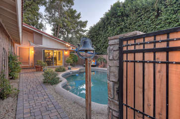 Charming front gate and dinner bell welcome you to paradise