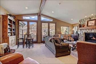 Family Room has a Stone Fireplace and Ample Natural Light