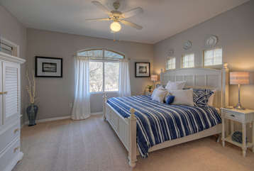 Cheerful and bright master bedroom features king bed, walk-in closet and large window with arched transom