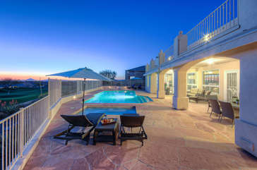 Exclusive patio extends length of home and is a private oasis of resort amenities that include pool and spa with swim-up bar
