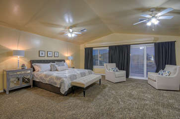 Trendy upstairs master bedroom has king bed and patio doors to balcony