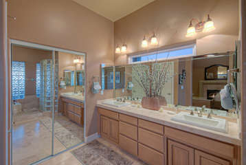 Bathroom in first floor master suite features double vanity sinks, large walk-in closet, garden tub and separate shower