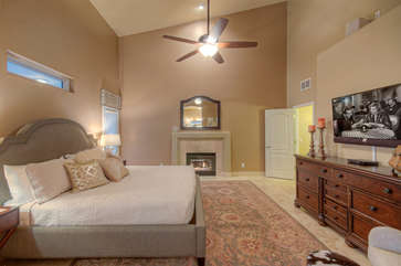 First floor master suite features a king bed, fireplace and large television