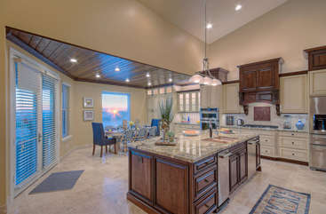 Warm, natural light from large windows and doors brightens kitchen and dining areas