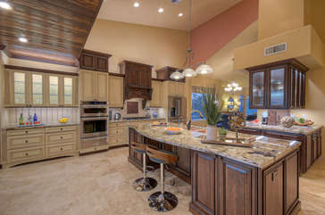 Kitchen island provides ample space for preparing and serving choice cuisine plus bar seating for two