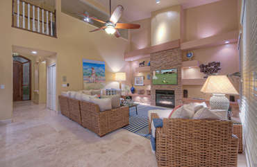 Great room is chic and cozy gathering place to enjoy gas fireplace and large television
