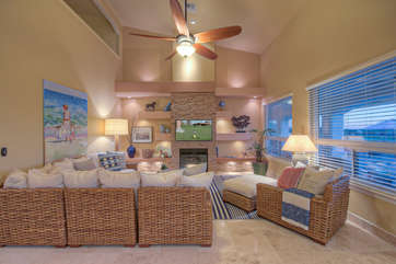 Friends and family will love stylish great room with comfortable seating and wall of windows