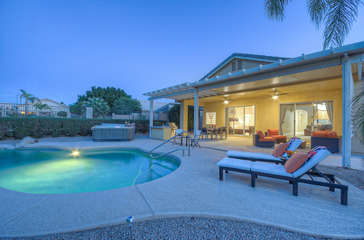 Covered patio transitions to professionally landscaped deck and yard with inviting pool