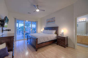 Television and doors to patio are appealing features in master bedroom