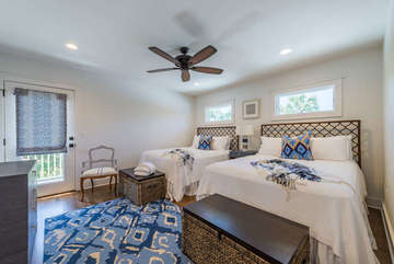 1st floor bedroom has two queen beds and hardwood floors.