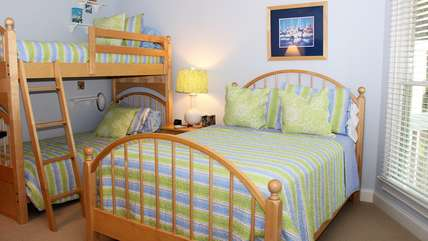 The second bedroom is decorated with pretty blue and green colors.