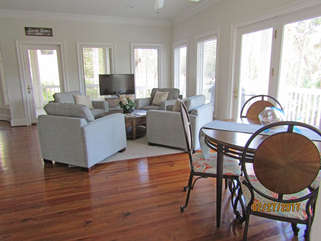 Large, open kitchen with two tables for eating, plus sitting area with another HDTV.